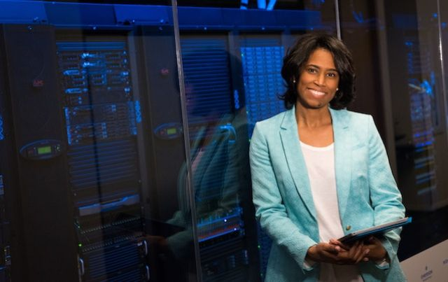 Businesswoman leaning against glass wall outside computer server room.