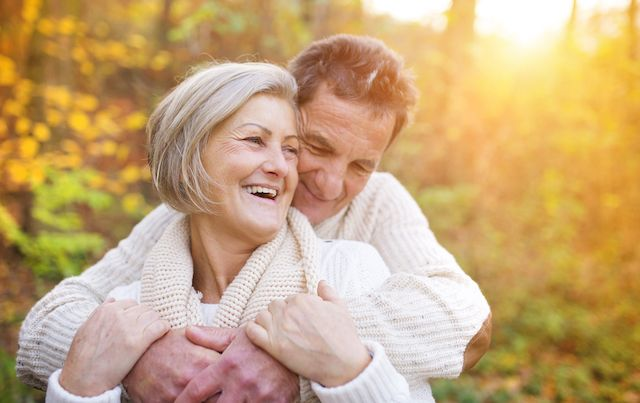 Older couple embracing in sun-dappled woods