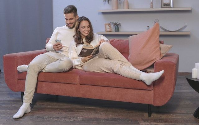 A couple relaxes together on a couch, reading and looking at the phone.