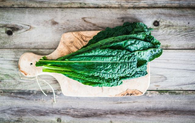 Kale leaves stacked on wooden cutting board atop plank table.