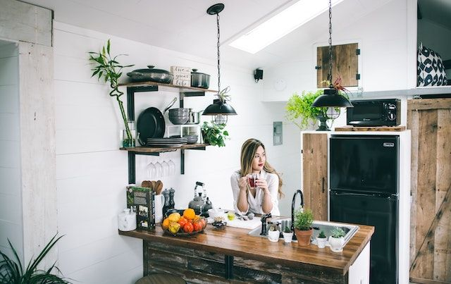 Woman sipping tea in her kitchen.
