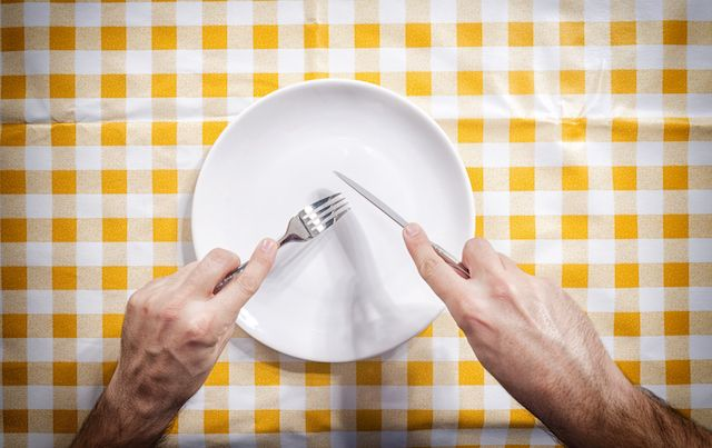 Hnds with knife and fork ready to eat from empty plate on yellow checked tablecloth.