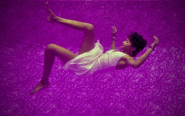 woman falling through purple background