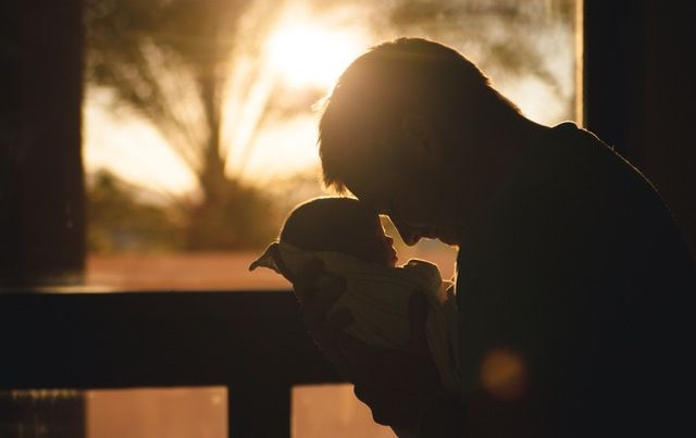 Father with forehead pressed to baby in silhouette in front of sunlit window.