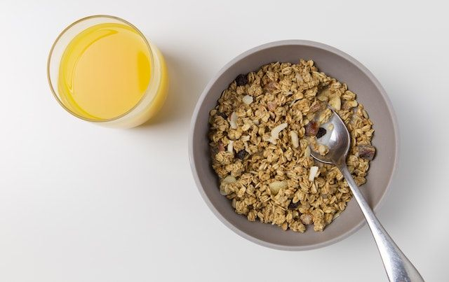 High fiber ceral in bowl with spoon and glass of orange juice