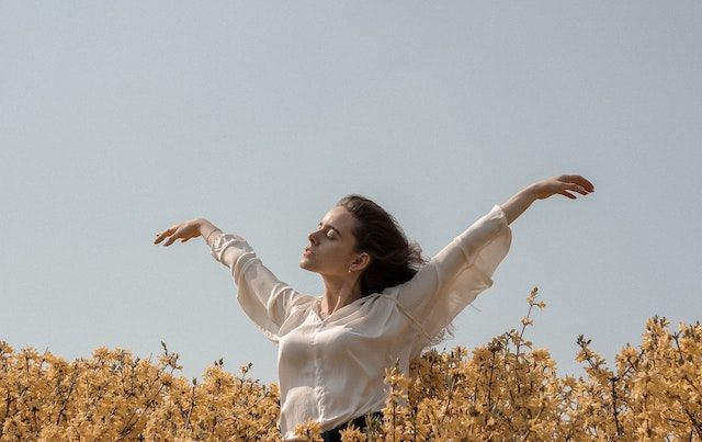 Woman in a field holding her arms open.