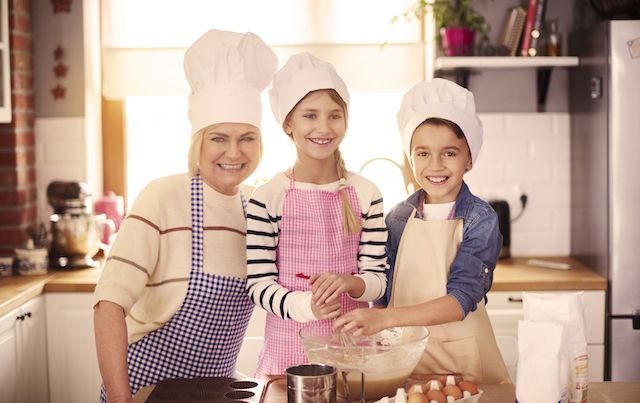 Grandmother and grand kids in kitchen with chef hats
