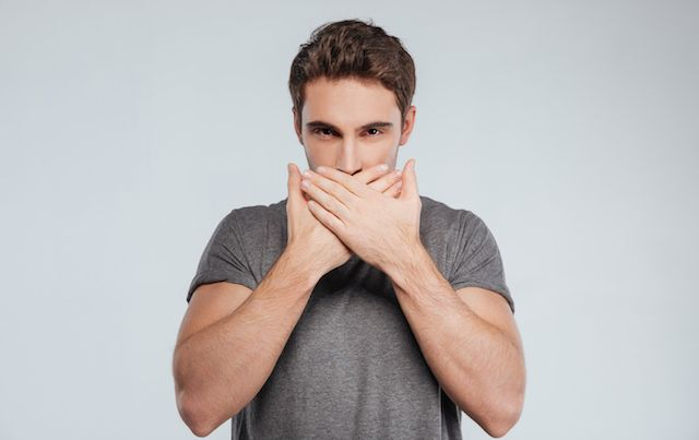 Man covering mouth with both hands to Shush