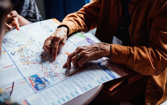 elderly hands on a map