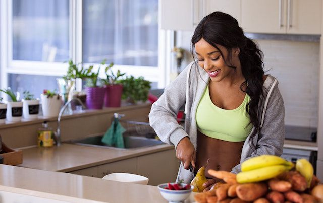 Healthy woman in kitchen cutting fruit for breakfast.