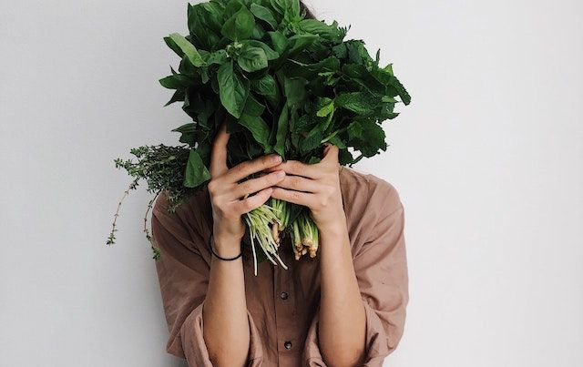 Woman hiding behind big bunch of spinach and other greens