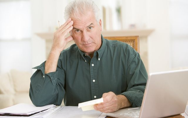 Man stressed out in home office with computer and paperwork.