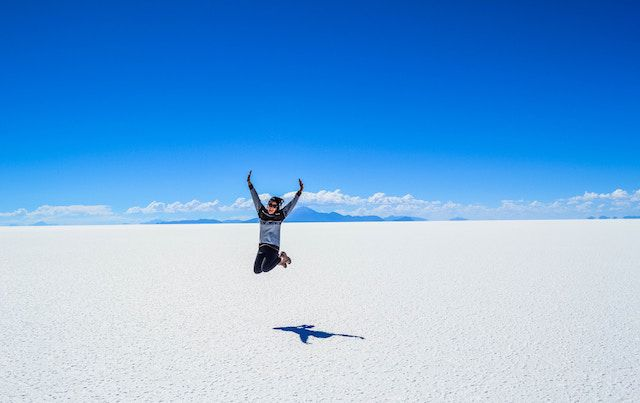 Person jumping for joy in snowy field with vivid blue sky.