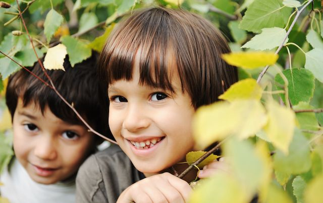 Two children smiling and peeking out from behind leaves and bushes