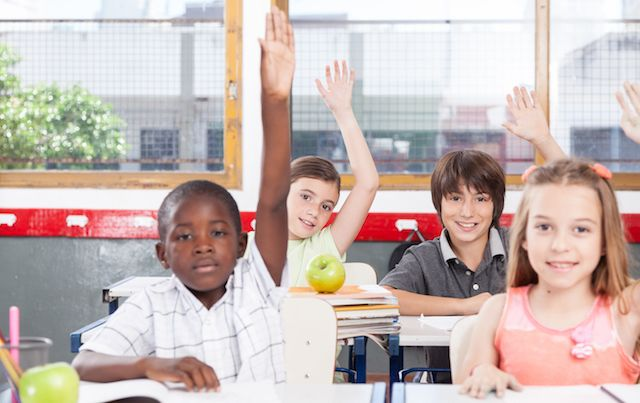 Four kids in a classroom raising their hands to answer a question.