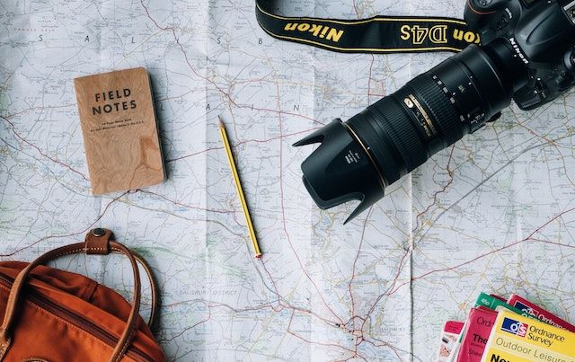 Camera, pamphlets, and luggage on top of maps