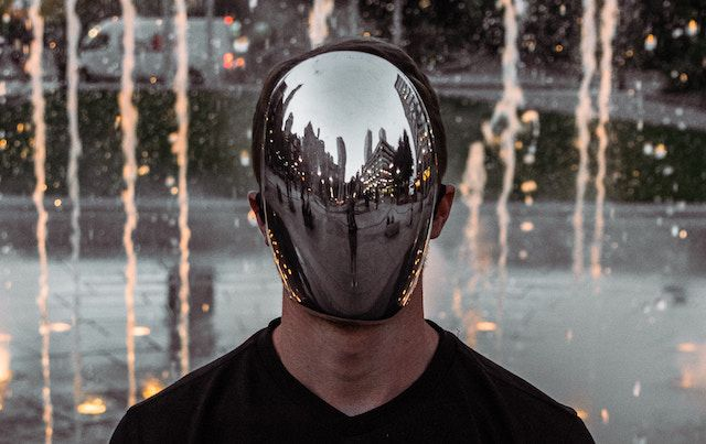 Man with chrome mirrored cover over his face