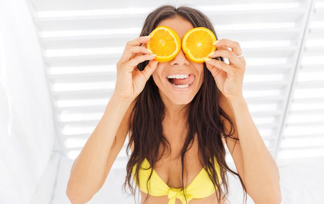 Woman holding orange slices up over her eyes.