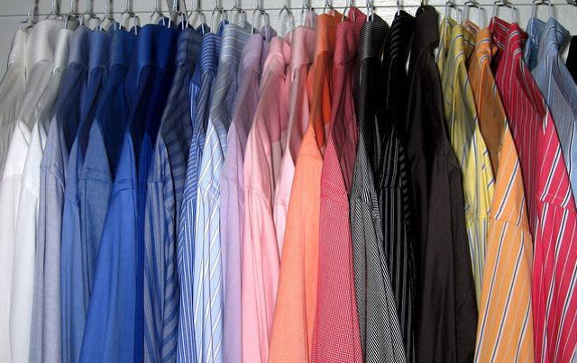 Clothes Hanging In Closet Arranged By Color