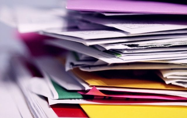 Close up of stacked documents and folders and paperwork.