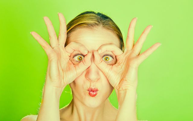 woman on green background with fingers around her eyes