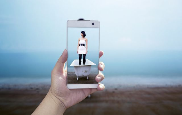 Close up of phone taking picture instead of real life on beach