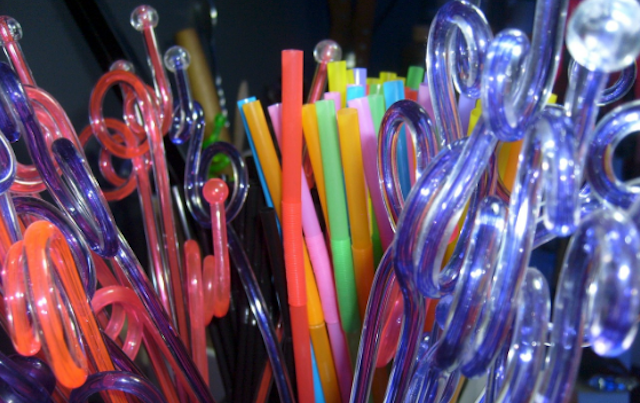 Jumble of colorful straight and twisty plastic straws.