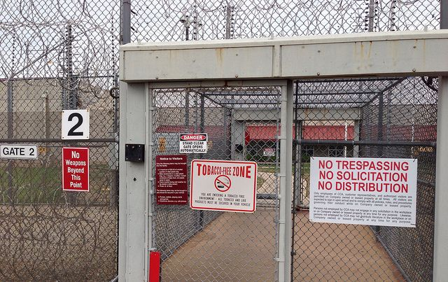 Prison gates with warning signage and barbed wire.
