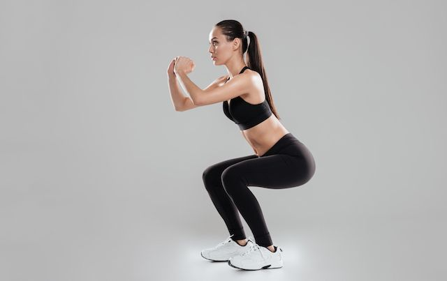 Woman in workout clothes demonstrating proper technique for a squat