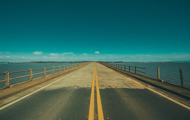 paved road bridge going off into horizon over water