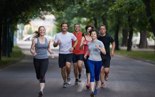 Group of adults on a run through a tree-lined street