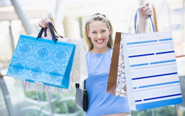 Proud woman showing off all her purchases and shopping bags.