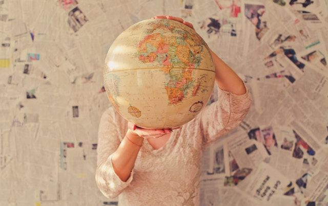 WOman holding world globe up in front of her face.