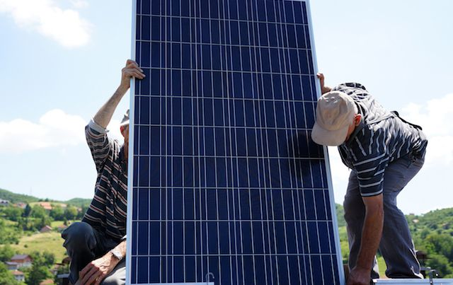 Two men installing solar panels on a rooftop.