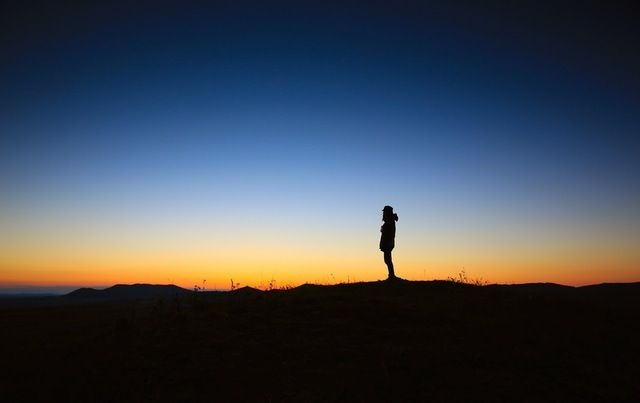 silhouette of lone hiker at dawn