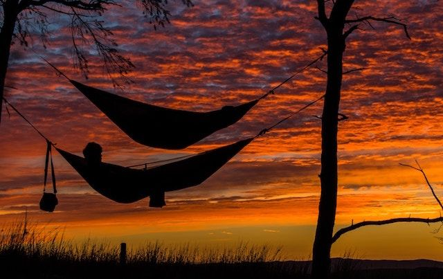 Two hammocks in silhouette against sunset sky