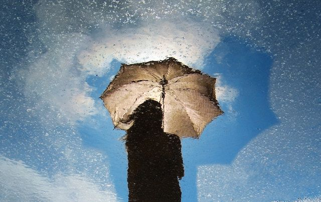 Rain soaked woman with umbrella against blue sky.