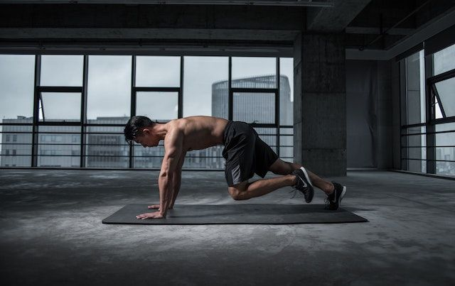 Man in pushup pike position on yoga mat in industrial loft space.