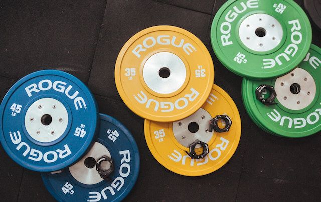 Gym weight plates from a barbell in green, yellow, and blue.
