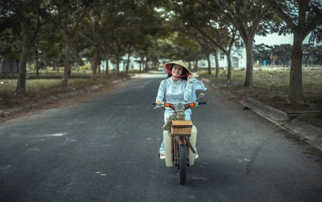 Woman on bike with basket wearing hat.