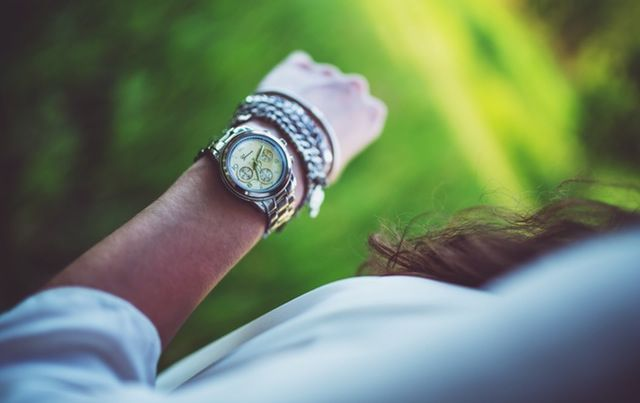 close up on woman's wrist with watch and bracelets