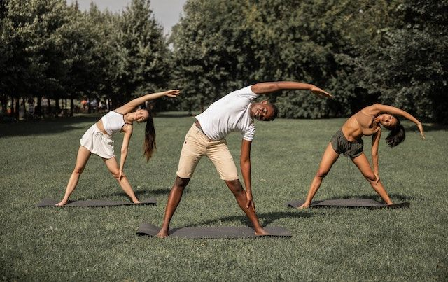 Three people in the park doing standing side bend yoga pose