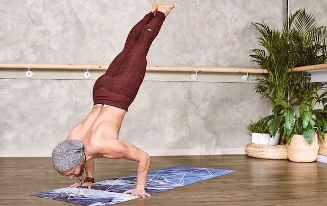 Shirtless man in yoga inversion pose.