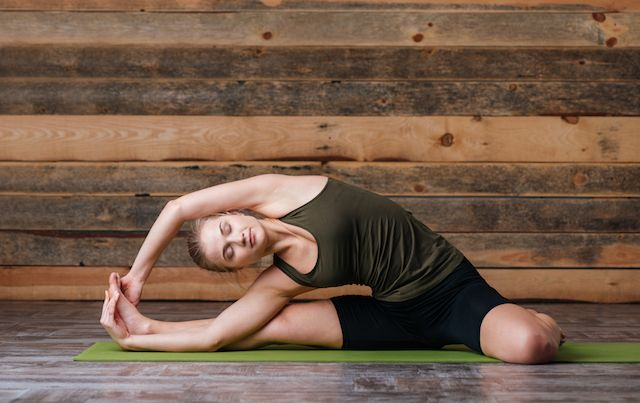 Young woman in yoga side stretch on floor in front of wooden wall