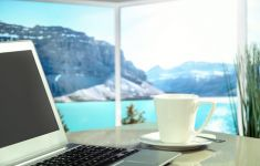 Computer and coffee cup on table in front of window with amazing mountain view