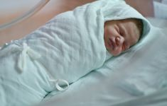 newborn baby tightly wrapped in swaddling blanket