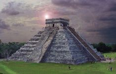 Chichen Itza temple with sun spots on cloudy day.