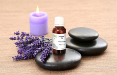 Bottle of lavender oil with lavender flowers, stones, and purple candle