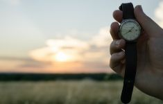 Hnad holding up wrist watch against sunrise sky