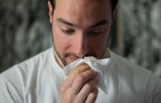 Man with allergies blowing nose with tissue